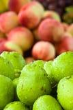 Close up das peras com os pêssegos no fundo imagem de stock