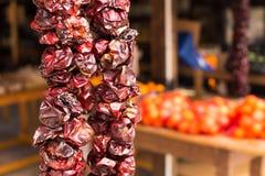 Close up das pimentas vermelhas secadas que penduram em uma corda no mercado imagem de stock