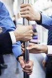 Close-up das quatro mãos de pessoa de negócio que guardam o polo no metro Fotografia de Stock Royalty Free