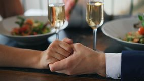Close-up dat van de mannelijke vrouwelijke hand van de handholding op lijst met champagneglazen en platen met voedsel wordt gesch stock footage