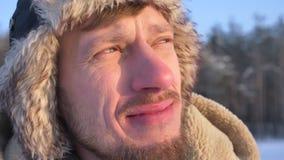 Close-up dat van ontdekkingsreiziger op middelbare leeftijd in kap en laag het letten op bij zon vreugdevol wordt geschoten stock footage