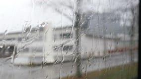 Close-up dat van regendalingen en stroken op de vensterod bewegende bus door stadsstraat wordt geschoten in de diepe herfst stock video