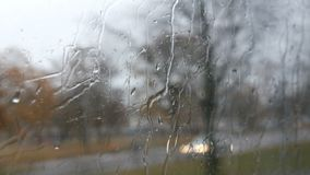 Close-up dat van regendalingen en stroken op de vensterod bewegende bus door stadsstraat wordt geschoten in de diepe herfst stock videobeelden