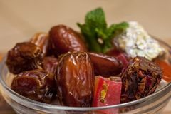 Close up with dates and middle eastern desserts with rose petals and turkish delight Royalty Free Stock Images