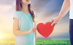 Close up of daughter and father holding red heart Stock Images