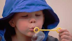 Close up de 5 bolhas de sopro do menino dos anos de idade Fotografia de Stock Royalty Free
