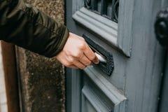 Close-up De brievenbesteller zet een brief of een krant of tijdschrift in de brievenbus bij de deur van een woningbouw of a royalty-vrije stock afbeeldingen