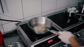 Close-up - de chef-kok die een garnaal in een pan op de keuken koken stock footage