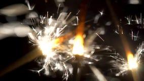 Close-up de chuveirinhos efervescentes na obscuridade Pouco fogos de artifício festivos do fogo em varas shinning brilhantemente  vídeos de arquivo