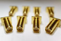 Close-up de componentes chapeados ouro dispersados da eletrônica dos conectores machos de SMA no foco parcial no fundo branco foto de stock