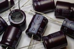 Close-up de componentes dispersados da eletrônica de poder do capacitor eletrolítico no fundo branco no teste padrão aleatório imagens de stock