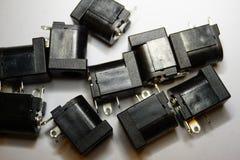 Close-up de componentes dispersados da eletrônica de poder do jaque da C.C. no fundo branco no teste padrão aleatório foto de stock