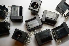 Close-up de componentes dispersados da eletrônica de poder do jaque da C.C. no fundo branco no teste padrão aleatório imagens de stock