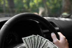 Close up de dólares americanos em uma roda Equipe a mão do ` s com dinheiro em um fundo preto do carro Conceito do investimento C Fotos de Stock Royalty Free