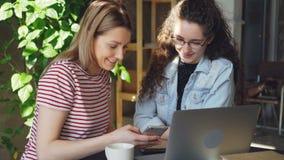 Close-up de dois estudantes fêmeas que usam o smartphone A menina loura atrativa está apontando o écran sensível e está conversan vídeos de arquivo