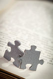 Close up de duas partes do enigma de serra de vaivém na página de um livro Fotografia de Stock