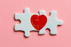 Close up de duas partes de um enigma com coração vermelho no fundo cor-de-rosa Fotografia de Stock Royalty Free