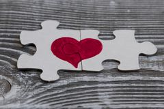 Close up de duas partes de um enigma que forma um coração em uma superfície de madeira rústica, Foto de Stock Royalty Free