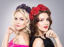 Close-up de duas senhoras bonitas que vestem faixas da flor Imagens de Stock Royalty Free