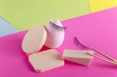 Close up de esponjas cosméticas, pestanas falsas, pinça no fundo colorido fotografia de stock