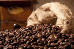 Close-up de feijões do coffe com saco e moedor do juta Fotos de Stock Royalty Free