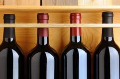 Close up de frascos de vinho vermelho no caso de madeira Imagens de Stock