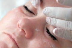 Close-up De handen van een schoonheidsspecialist of een arts in witte handschoenen zetten oogroom op het gezicht van een volledig royalty-vrije stock fotografie