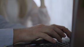 Close-up de handen van mensen actief en snel type op het toetsenbord van laptop Het wijfje op de achtergrond helpt richtend stock videobeelden