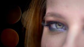 Close-up de helft-gezicht spruit van jong mooi vrouwelijk gezicht met ogen sloot met blije gelaatsuitdrukking met bokehlichten stock video