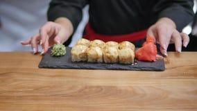 Close-up - de kelner zette aan boord de sushi op de lijst in restaurant Royalty-vrije Stock Foto's