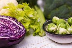 Close-up de legumes frescos sortidos em uma tabela de madeira branca: couve, brócolis, couve-flor e couve-de-bruxelas e Imagem de Stock Royalty Free