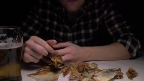 Close-up De mannelijke handen maken de gezouten droge vissen in nacht schoon Een mens bij nacht het eten vist en het drinken bier stock footage