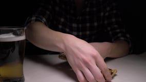 Close-up De mannelijke handen maken de gezouten droge vissen in nacht schoon Een mens bij nacht het eten vist en het drinken bier stock video