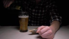 Close-up De mannelijke handen maken de gezouten droge vissen in nacht schoon Een mens bij nacht het eten vist en het drinken bier stock videobeelden