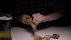 Close-up De mannelijke handen maken de gezouten droge vissen in nacht schoon 4K stock footage