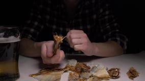 Close-up De mannelijke handen maken de gezouten droge vissen in nacht schoon 4K stock video