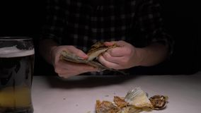 Close-up De mannelijke handen maken de gezouten droge vissen in nacht schoon 4K stock videobeelden