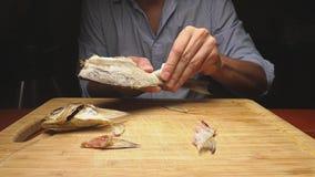 Close-up De mannelijke handen maken de gezouten droge vissen schoon Op de scherpe raad 4k langzame motie stock footage