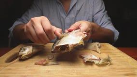 Close-up De mannelijke handen maken de gezouten droge vissen schoon Op de scherpe raad 4k langzame motie stock videobeelden