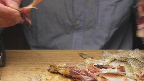 Close-up De mannelijke handen maken de gezouten droge vissen schoon Op de scherpe raad 4k langzame motie stock video