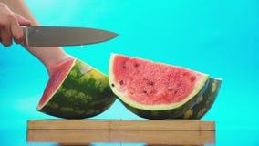 Close-up De mensen` s handen snijden de watermeloen in stukken Achtergrond voor een uitnodigingskaart of een gelukwens 4K Langzam stock footage