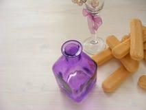 Close up de muitas cookies de Savoiardi com garrafa e vidro violetas em uma tabela branca do vintage com espaço da cópia fotos de stock