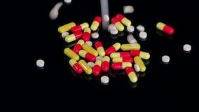 Close up de muitos comprimidos brancos que caem na tabela preta vídeos de arquivo