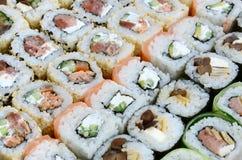 Close-up de muitos rolos de sushi com enchimentos diferentes Tiro macro do alimento japonês clássico cozinhado Imagem de fundo fotografia de stock royalty free
