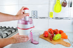 close-up De onherkenbare mens drukt biet binnen juicer om smakelijk sap voor ontbijt van verse groenten te maken, giet in transpa Stock Fotografie