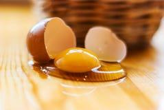 Close up de ovo quebrado na mesa de cozinha, defocuses da cesta GR Fotografia de Stock Royalty Free