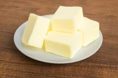Close-up de partes frescas da manteiga em uma placa branca Placa com manteiga em um fundo de madeira marrom Manteiga do sandu?che imagens de stock