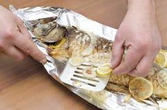 Close up de peixes grelhados da carpa na folha com limão, cebola Mãos masculinas que guardam a espátula com fatias de limão imagem de stock royalty free