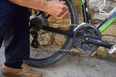 Close-up de Person Hands Lubricating Bike Chain imagem de stock