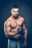 Close up de pesos de levantamento musculares de um homem novo Fotografia de Stock Royalty Free